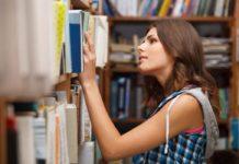 Девушка ищет книгу в библиотеке